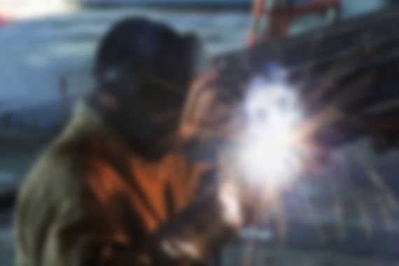 worker welding with electric arc electrode